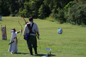 a parent and child shoot archery together at Battle on the Bay
